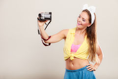 Happy pin up girl woman filming with camcorder. Royalty Free Stock Images