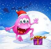 A happy pink beanie monster wearing Santa's hat Royalty Free Stock Image