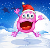 A happy pink monster jumping with a red hat Stock Photo