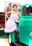 Happy Pinup Girl Sitting on Old Truck. Beautiful smiling retro pinup girl sitting on the fender of an old green truck symbolic of vintage Americana Stock Photography