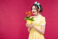 Happy pinup girl stamding and smelling orange flower in pot Royalty Free Stock Photography