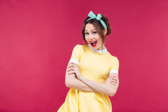 Happy pinup girl in yellow dress standing with arms crossed Stock Image