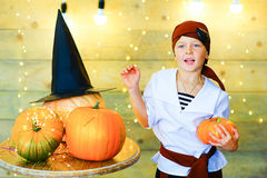 Happy pirate children during Halloween party. Playing around the table with pumpkins Royalty Free Stock Photography