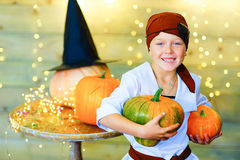 Happy pirate children during Halloween party. Playing around the table with pumpkins Royalty Free Stock Photos