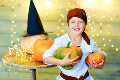 Happy pirate children during Halloween party. Playing around the table with pumpkins Stock Image