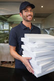 Happy pizza delivery man holding many pizza boxes Royalty Free Stock Photo