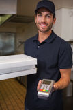 Happy pizza delivery man showing credit card machine Stock Image