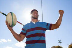 Happy player holding rugby ball with arms raised against blue sky. Low angle view of happy player holding rugby ball with arms raised by goal post against blue Royalty Free Stock Photography