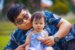 Happy playful Asian Korean man as loving father enjoying sweet and beautiful baby girl daughter sitting together playing on grass stock photo