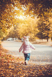 Happy playful baby in the autumn park Stock Photo
