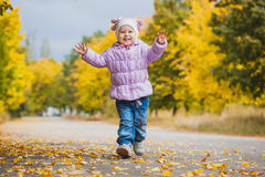 Happy playful baby is running in the autumn park Royalty Free Stock Photography