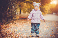 Happy playful baby is running in the autumn park Stock Photo