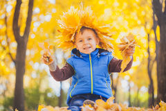 Happy playful boy have fun in the yellow leaves Royalty Free Stock Photos