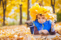 Happy playful boy have fun in the yellow leaves Stock Photography