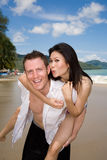 Happy playful couple at the be. Caucasian man & asian woman having fun carrying piggyback at the beach Royalty Free Stock Images