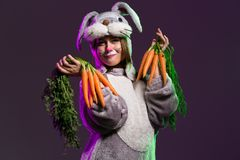 Happy and playful Easter bunny girl with carrots. Cute and playful girl in a full body bunny suit with big ears. Holding carrots. Dark colored background Stock Images