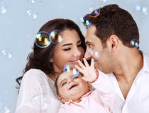 Happy playful family. Closeup portrait of happy young family playing with soap bubbles  on blue background, having fun, playing game, happiness and joy concept Royalty Free Stock Image