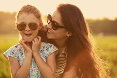 Happy playful fashion kid girl embracing her mother in trendy sunglasses in profile view and looking on nature background. Closeup stock photo
