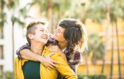 Happy playful women girlfriends in love sharing time together. Happy playful girlfriends in love sharing time together at travel trip on piggyback hug - Women Stock Image