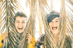 Happy playful girlfriends in love sharing time together at travel. Trip playing with palm tree - Women friendship concept with girls couple having pure fun Royalty Free Stock Image