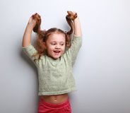 Happy playful kid girl in blouse holding hair Royalty Free Stock Photos