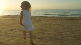 Happy playful little girl in white dress running on the beach sand stock footage