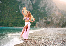 Happy playful woman on sea beach on background of mountains Royalty Free Stock Images