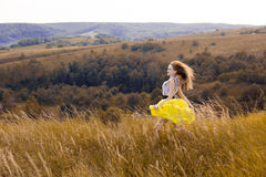 Happy playful young pretty girl running on the field with green, yellow wheat on the way to good life.Happy adventure in summer, s Royalty Free Stock Image