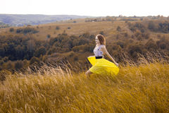 Happy playful young pretty girl running on the field with green, yellow wheat on the way to good life.Happy adventure in summer, s Royalty Free Stock Photography