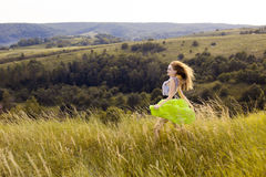 Happy playful young pretty girl running on the field with green, yellow wheat on the way to good life.Happy adventure in summer, s Royalty Free Stock Images