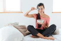 Happy playful young woman covered her eye with spoon. And sitting on bed in bedroom Royalty Free Stock Photo