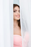 Happy playful young woman hiding behind white curtains and smiling Stock Image