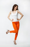 Happy playful young woman in orange pants posing on neutral back Stock Photo