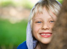 Happy playing child peeking from behind a tree. With green copy-space Royalty Free Stock Photos
