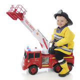Happy Playing Fireman. An adorable toddler boy happily riding a toy firetruck in his fireman`s outfit.  On a white background Royalty Free Stock Image