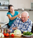 Happy playing mature couple cooking food Stock Photography