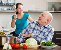 Happy playing mature couple   in home kitchen Stock Images