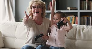 Happy senior grandmother playing online video games with small granddaughter.