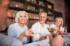 Happy pleasant people talking about wine round the table royalty free stock photography
