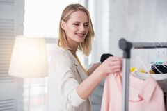 Happy pleased businesswoman selecting garments for showroom. First showroom. Satisfied glad businesswoman taking garment from stand while smiling Royalty Free Stock Photo