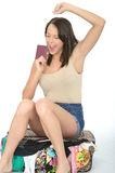 Happy Pleased excited Young Woman Holding a Passport Sitting on an Overflowing Suitcase Stock Images