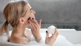 Happy pleased girl enjoying applying face cream to smooth pure face skin close-up in bathroom. Smiling young female making beauty skincare procedure taking stock video