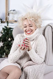 Happy and pleased woman waiting for the New Year. Holiday sitting in a chair and drinking fragrant a hot beverage. Series of winter holiday photos. eyes closed Royalty Free Stock Photography