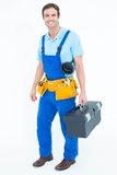 Happy plumber carrying tool box. Full length portrait of happy plumber carrying tool box over white background Royalty Free Stock Photo