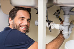Happy plumber fixing under the sink Stock Image