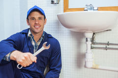 Happy plumber holding wrench sitting next to sink Royalty Free Stock Photos