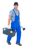 Happy plumber with plunger and toolbox walking on white background Stock Photo
