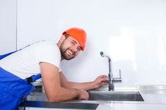 A plumber worker, in uniform, assures the quality of the installation of the crane in the kitchen. A happy plumber worker, in blue uniform and an orange helmet Stock Photography