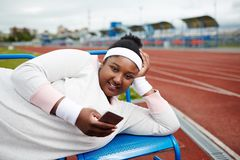 Girl with gadget. Happy plus-size African-american girl in white sweatshirt, wristbands and headband lying on bench at stadium and texting in smartphone Stock Photo