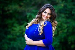 Happy plus size fashion model in blue dress outdoors, happiness beauty woman with professional makeup and hairstyle. On nature Stock Photo